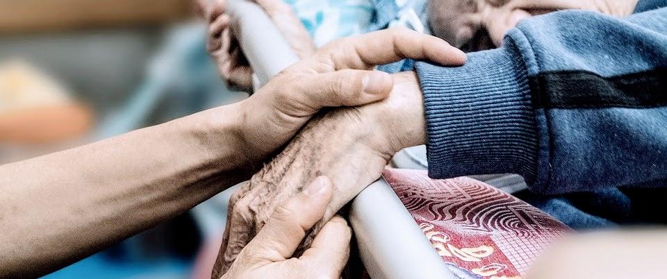 Mãos jovens segurando mão de idoso