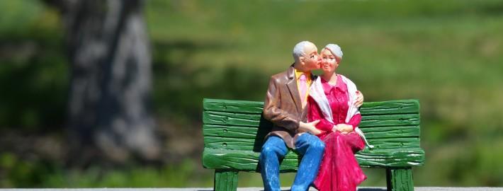 Escultura casal de idosos sentados em bano de praça